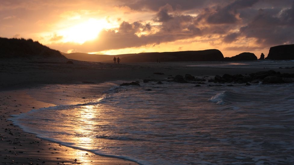 People on a Shetland beach at sunset