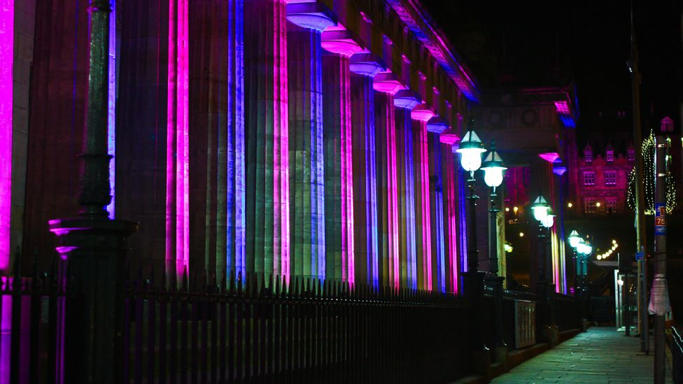 Pillars of the National Gallery of Scotland lit up at night with pink and purple lights