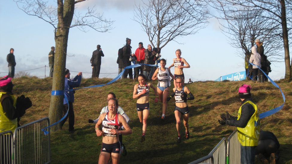 Cross country runners cheered on by spectators