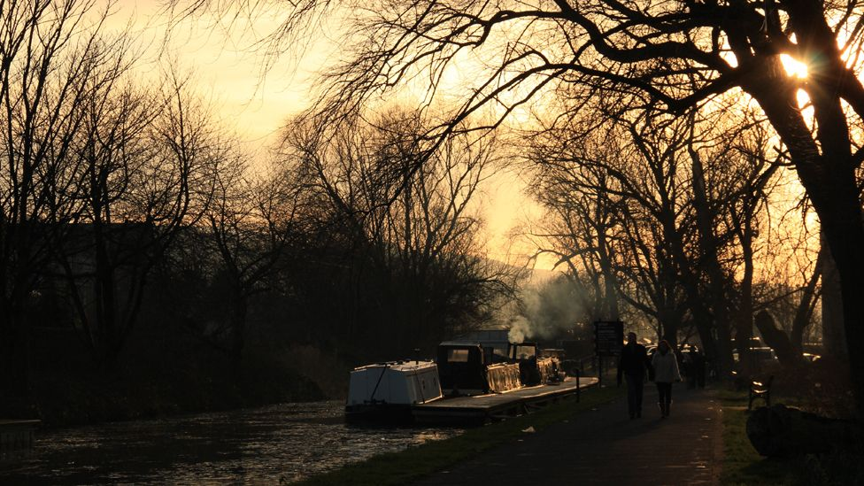 People walking by a barge on a canal