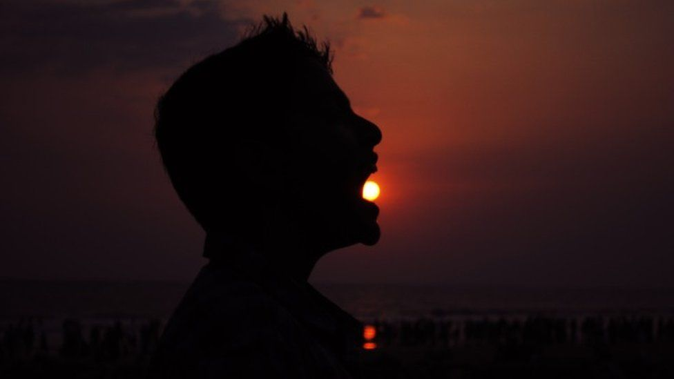 Man appears to swallow the Sun