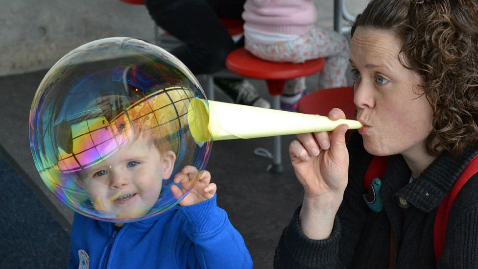 Ewan watches his mum blowing a bubble