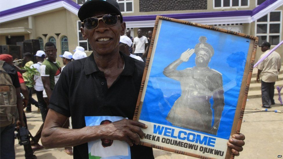 A man holds a picture of Chukwuemeka Ojukwu