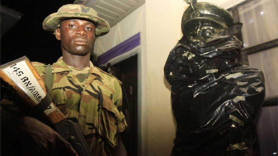 A soldier stands guard next to a partially wrapped statue of Chukwuemeka Ojukwu