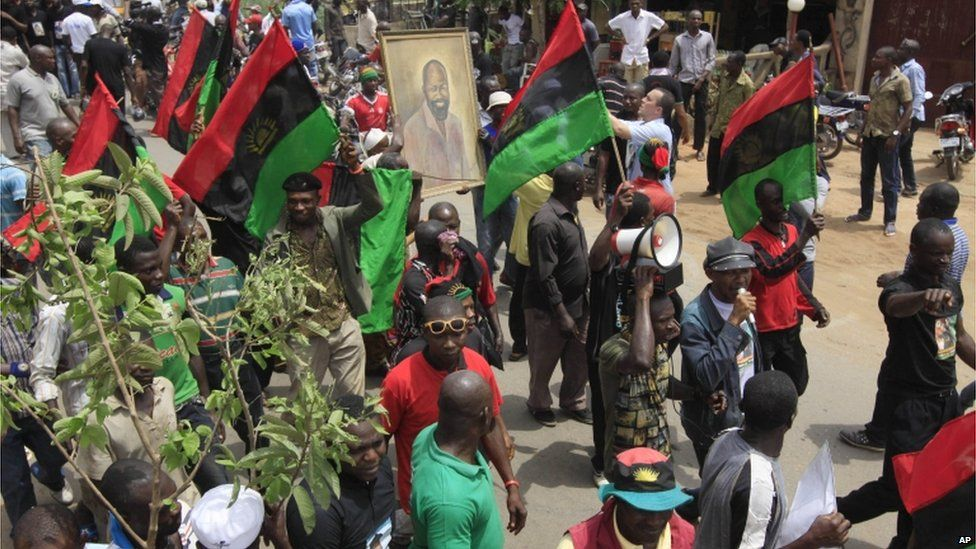 people holding a portrait of Col Ojukwu and waving Biafran flags