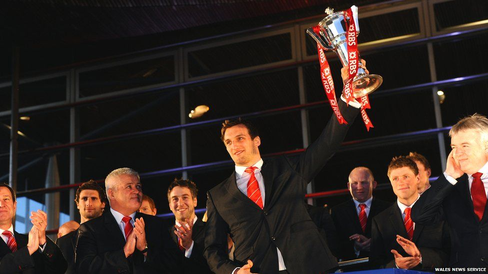 Wales coach Warren Gatland looks on as captain Sam Warburton lifts the Six Nations trophy