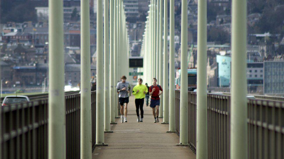 Runners on the pedestrian walkway of the Tay Road Bridge