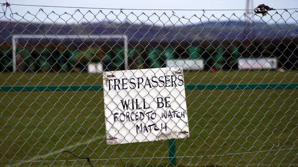 Sign pinned to a football pitch