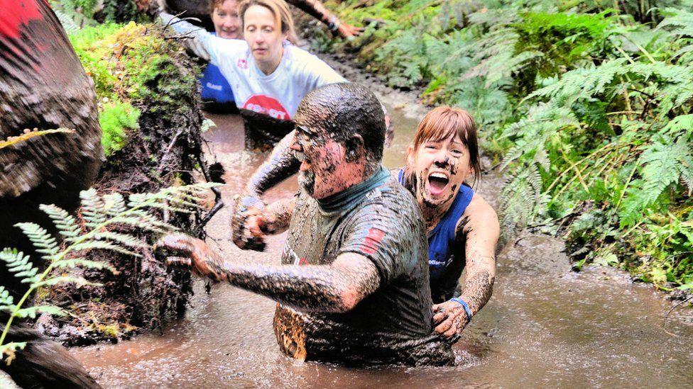 People wading through mud