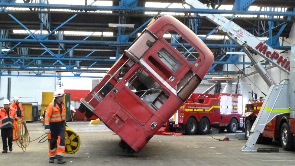 Crane lifting a bus into position in a garage