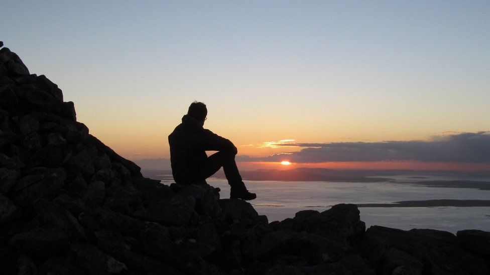 Man looking at sunset over Isle of Harris