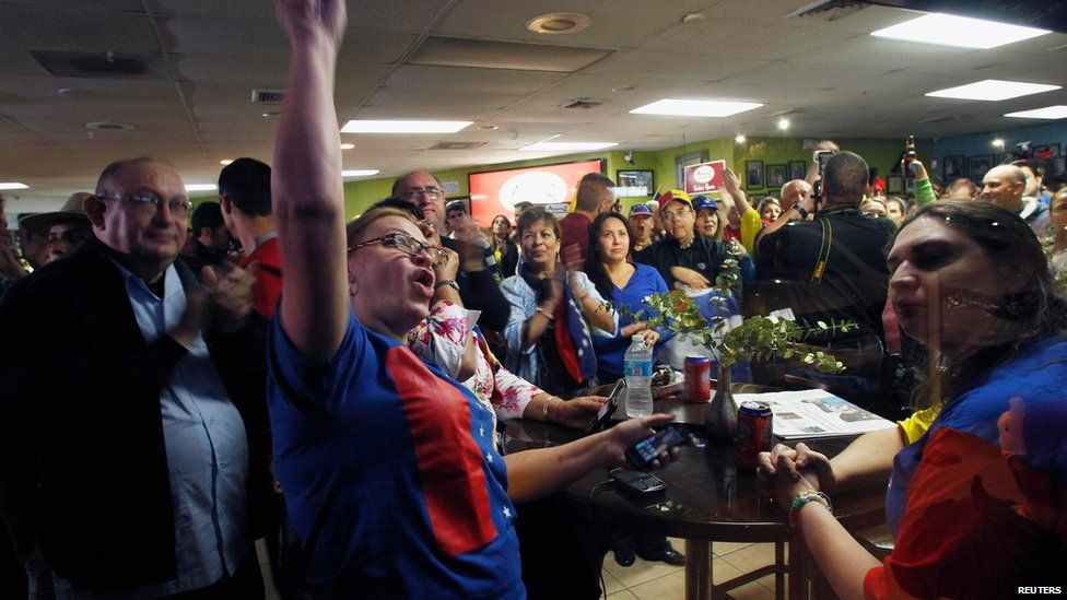A crowd cheers at a restaurant where opponents had gathered to celebrate following the death of Venezuelan President Hugo Chavez in Doral, Florida, on Tuesday