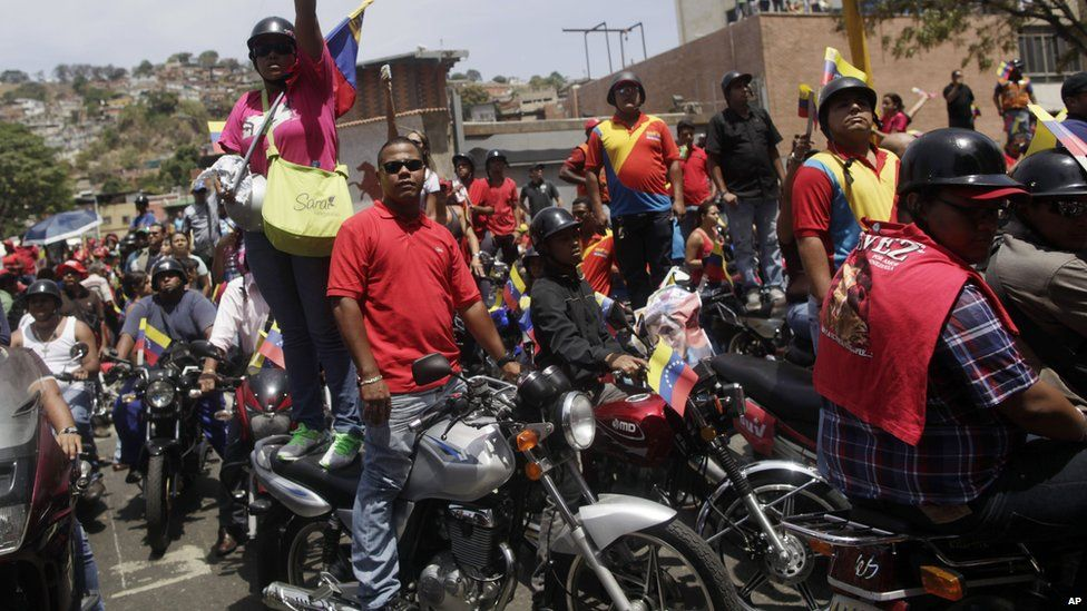 Chavez supporters on motorbikes try to catch a glimpse of his coffin