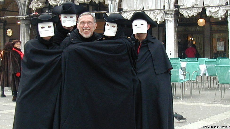 Four masked carnival performers with a tourist