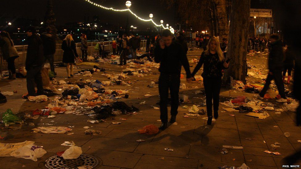 A couple walk along a street covered with litter