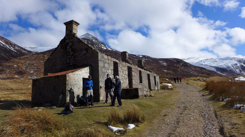 Walkers outside the remains of a croft house