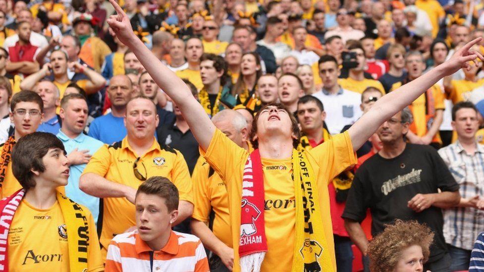 Cefnogwyr Casnewydd yn mwynhau'r awyrgylch y tu mewn i stadiwm Wembley.
