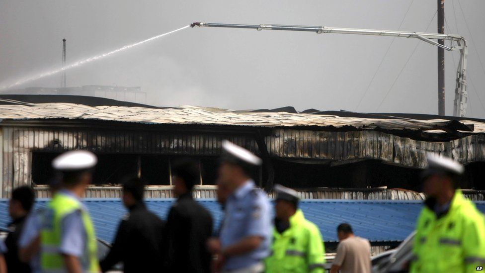 A water cannon douses down the roof of a poultry processing plant after a major fire in Dehui, north-east China's Jilin province, 3 June 2013