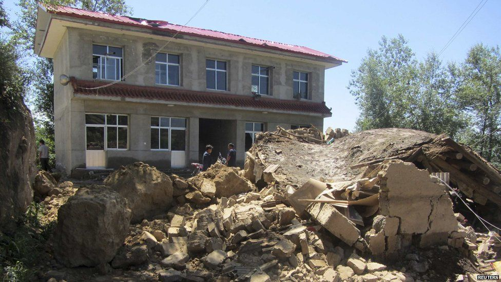 People stand next to a collapsed house after an earthquake struck Minxian county in China's north-west Gansu province on 22 July, 2013.