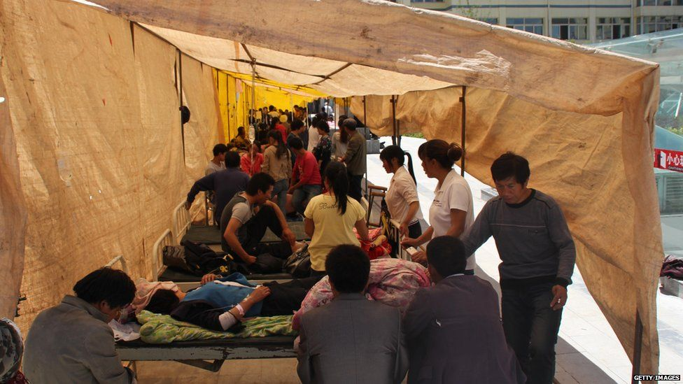 Injured residents get treatment in a makeshift hospital after an earthquake hit Minxian county in north-west China's Gansu province on 22 July 2013.
