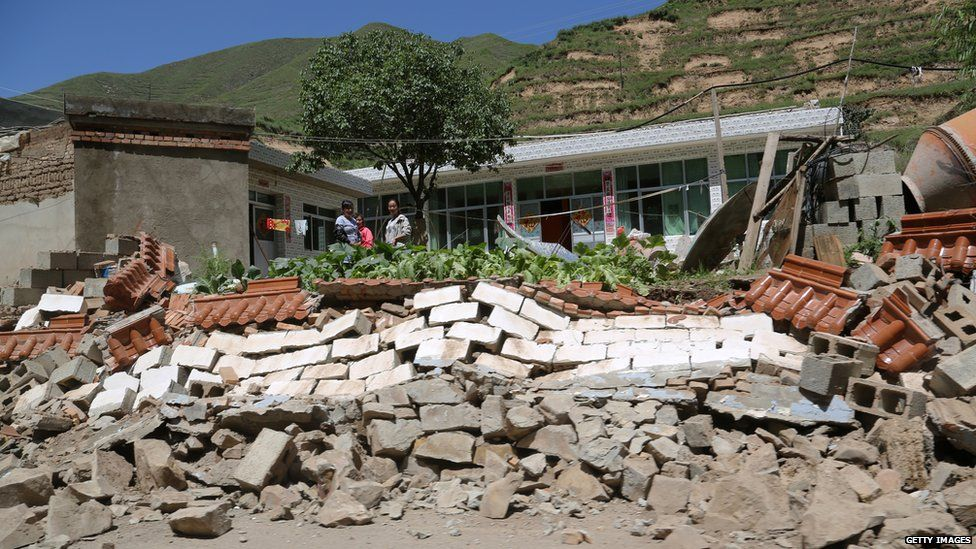 People look at a collapsed wall after an earthquake struck Hetuo township in China's north-west Gansu province on 22 July, 2013.