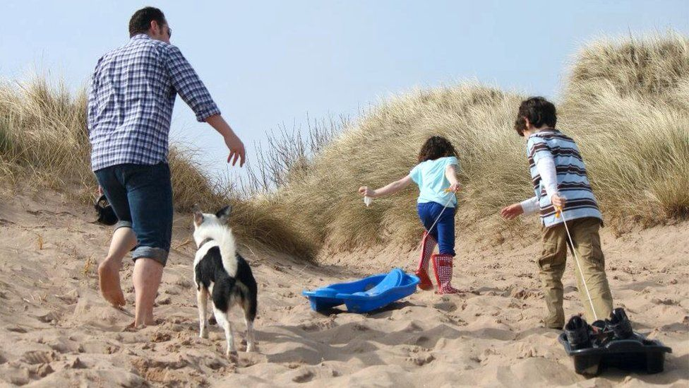 Family walking along sand dunes