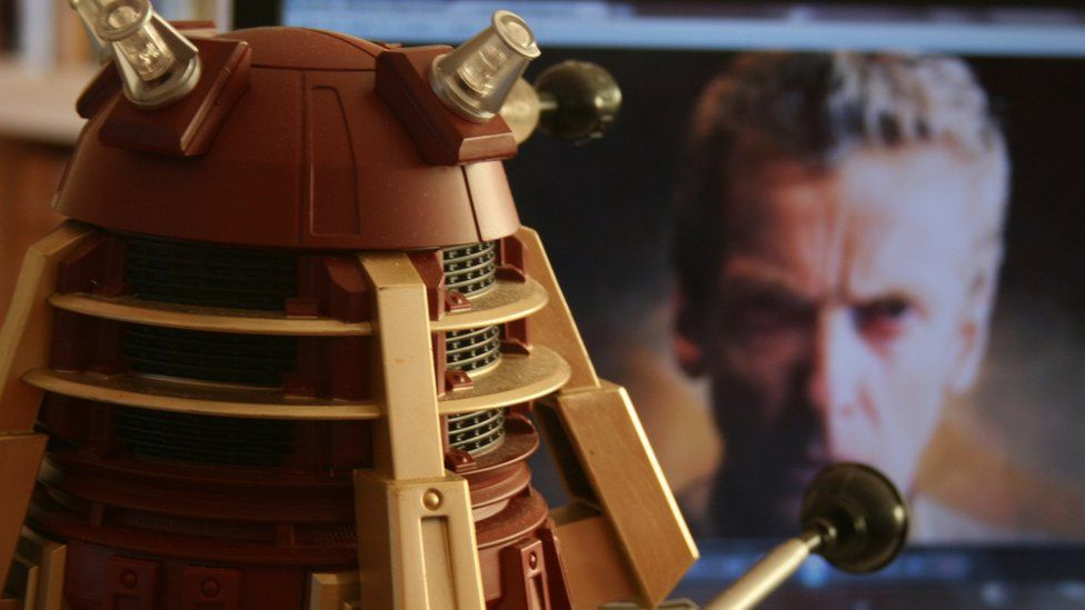 Dalek with Peter Capaldi on a TV screen in the background
