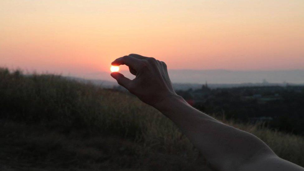 Woman appearing to hold the sun in her fingers