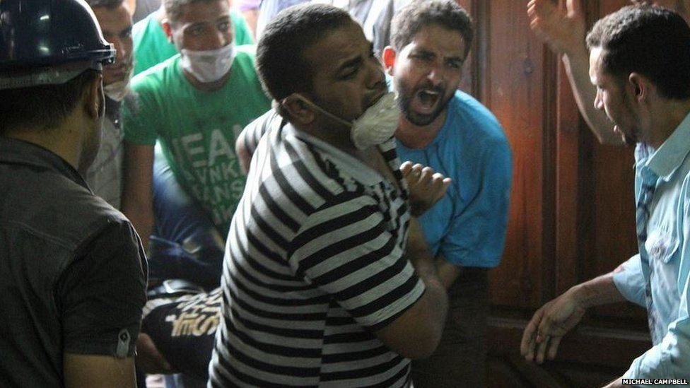 Protesters carry a casualty into a makeshift hospital inside a nearby mosque in Giza