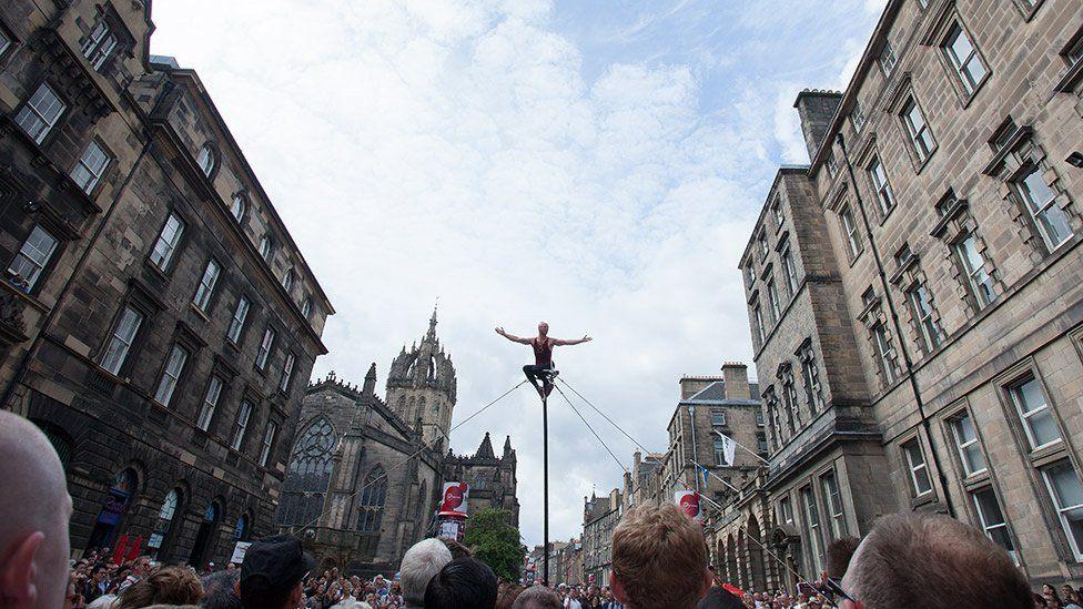 Man balances on a pole
