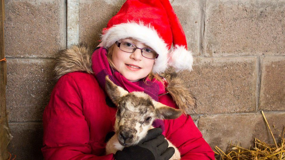 Megan with newborn lamb at Eden Brook Farm in Berwickshire