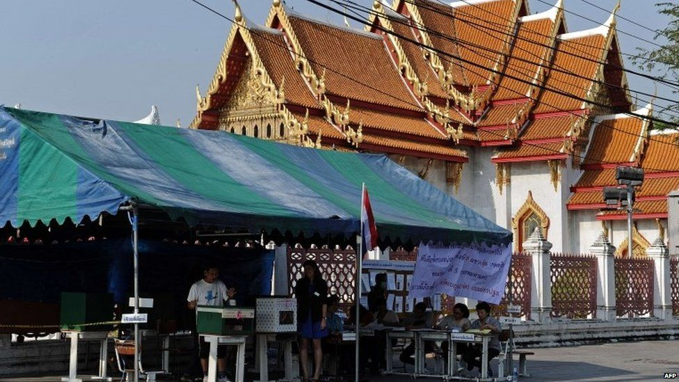 A Thai voter (L) casts his vote at an outdoor polling station in central Bangkok