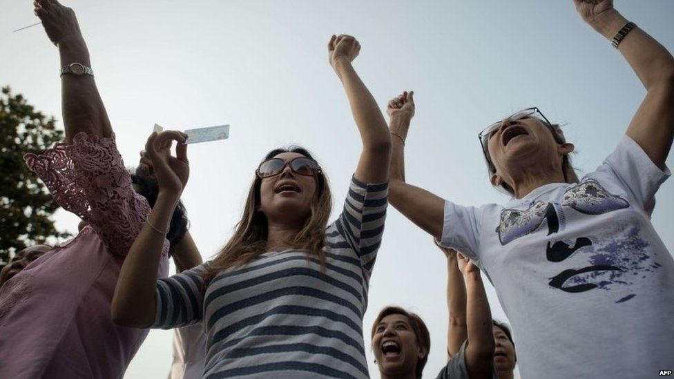 Thai people who can't go cast their votes in their district show their national identification card and shout slogans