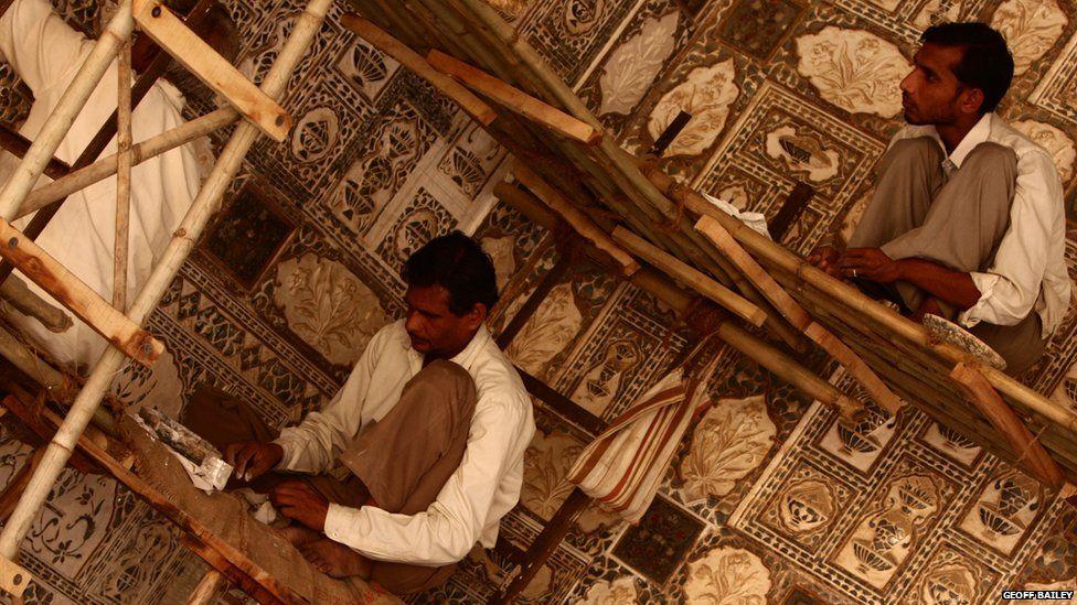 Three workers restoring a part of the Taj Mahal