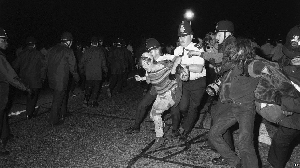 A vocal protest by a female hippy while being taken away by police at Amesbury, close to Stonehenge in June 1989