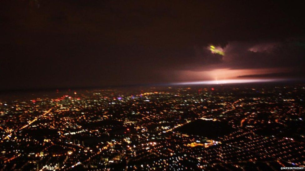 London at night as seen from a helicopter - with a lightning strike in the distance