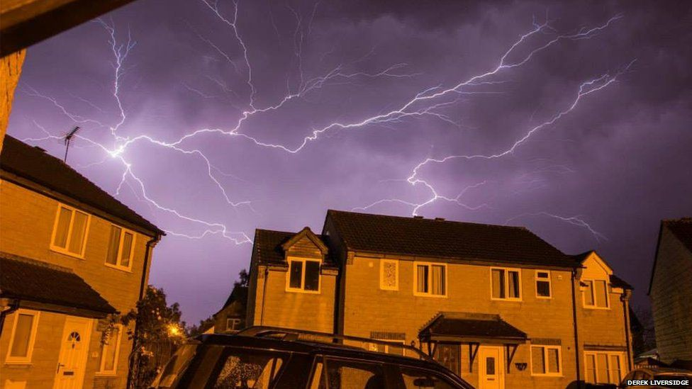 Lightning seen over houses at night
