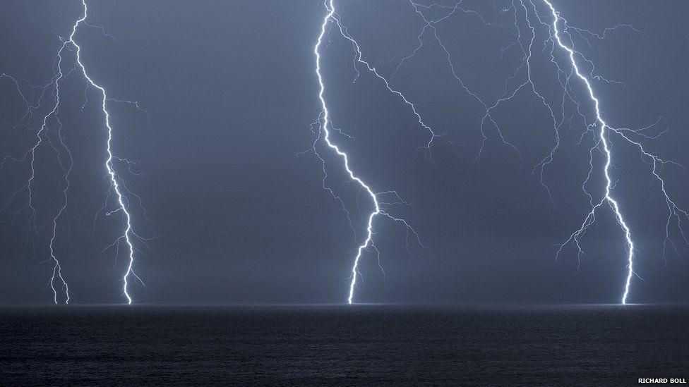 Three bolts of lightning hitting the sea