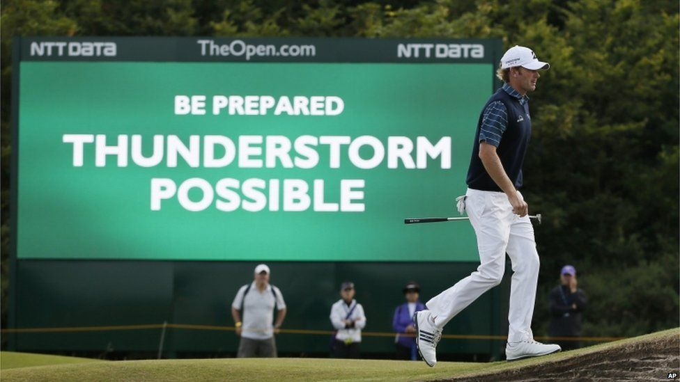 """Golfer Brandt Snedeker walks past a sign which says: """"Be prepared. Thunderstorm possible."""""""
