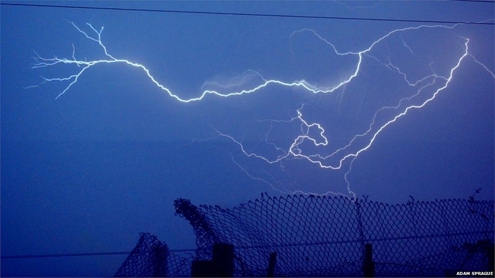A lightning strike. A wire fence can be seen in the foreground