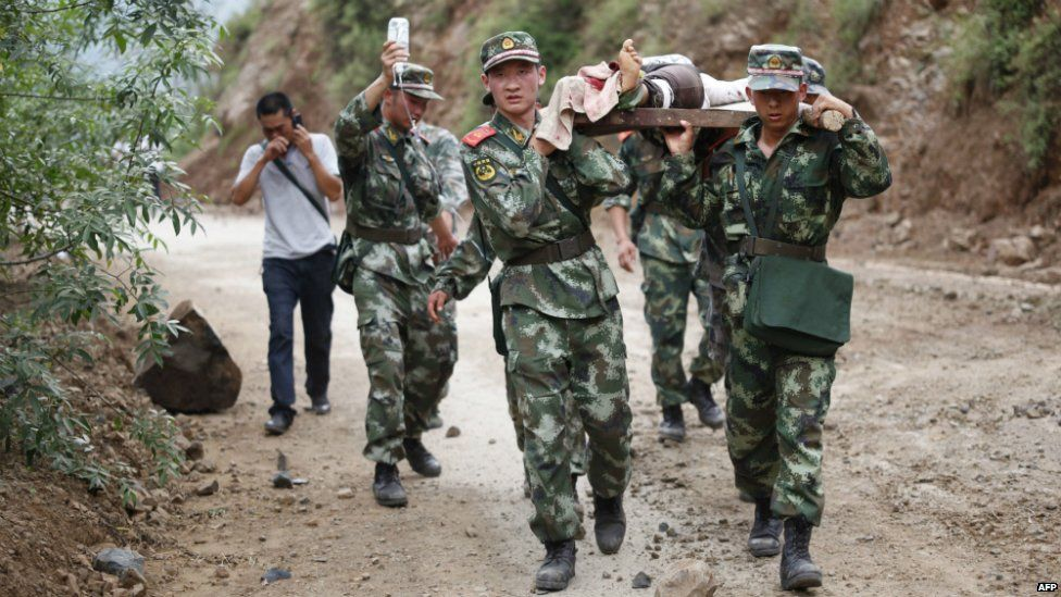 Chinese rescue workers carry an injured resident on a stretcher after the earthquake in Yunnan province - 3 August 2014