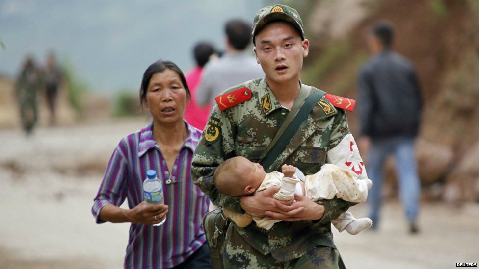 A member of the Chinese military carries a baby in his arms after the earthquake in Yunnan province - 3 August 2014