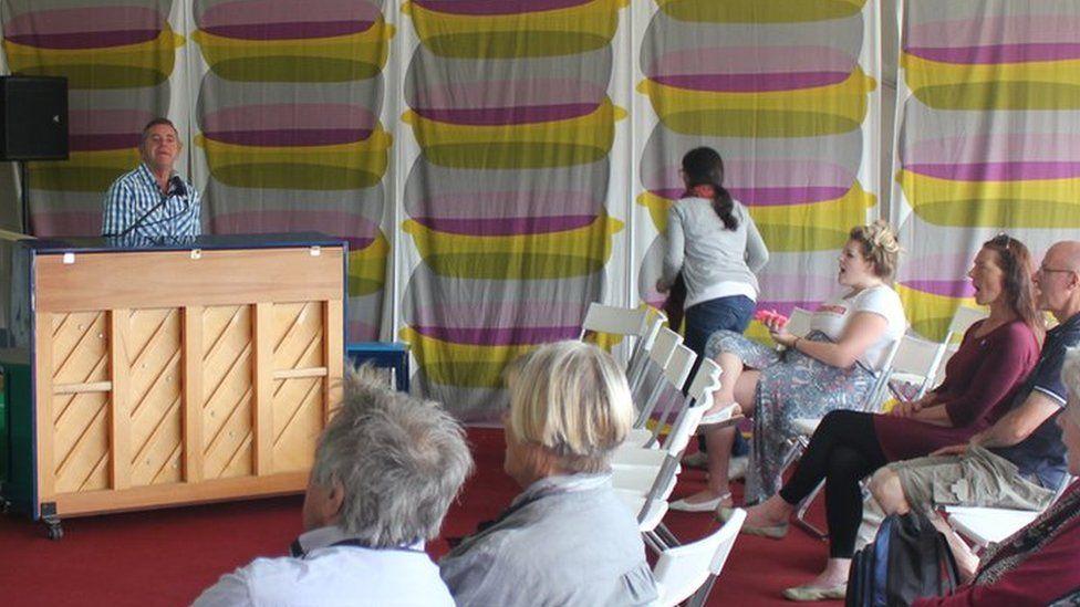 Aled Hall yn canu wrth biano / Aled Hall singing behind a piano