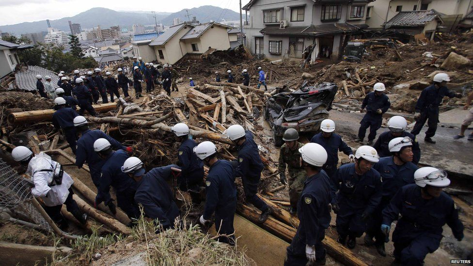 Police officers move to higher ground after an announcement to evacuate due to another landslide, as they search for survivors at the site where Wednesday's landslide swept through a residential area at Asaminami ward in Hiroshima, western Japan, on 22 August, 2014