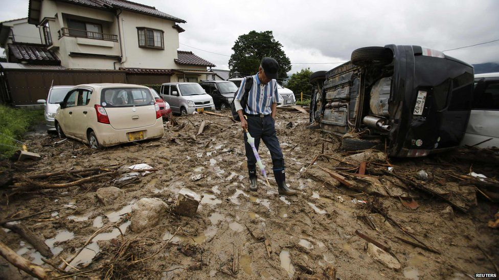 A man walks at a site where a landslide swept through a residential area at Asaminami ward in Hiroshima, western Japan, on 22 August, 2014