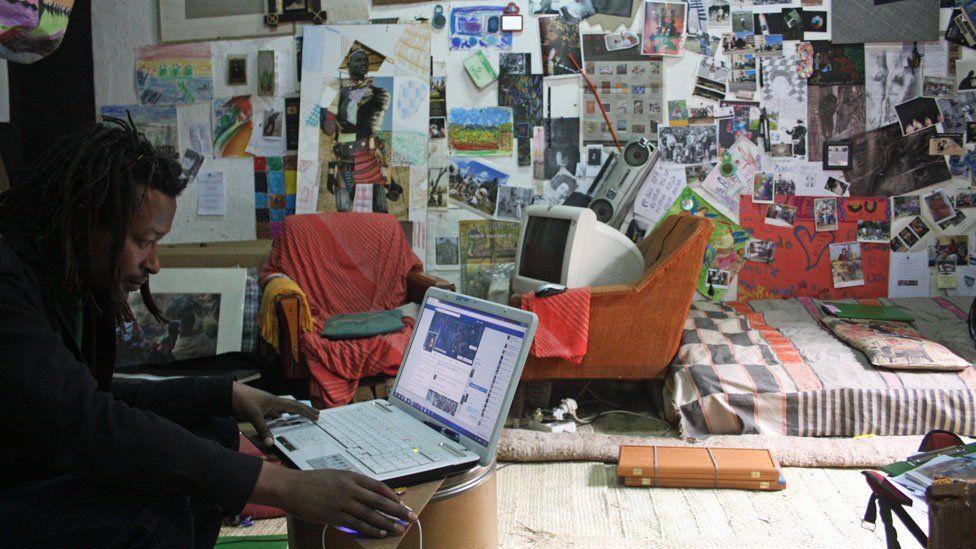 Artist Tamrat Gezahegn working on a laptop in Addis Ababa, Ethiopia