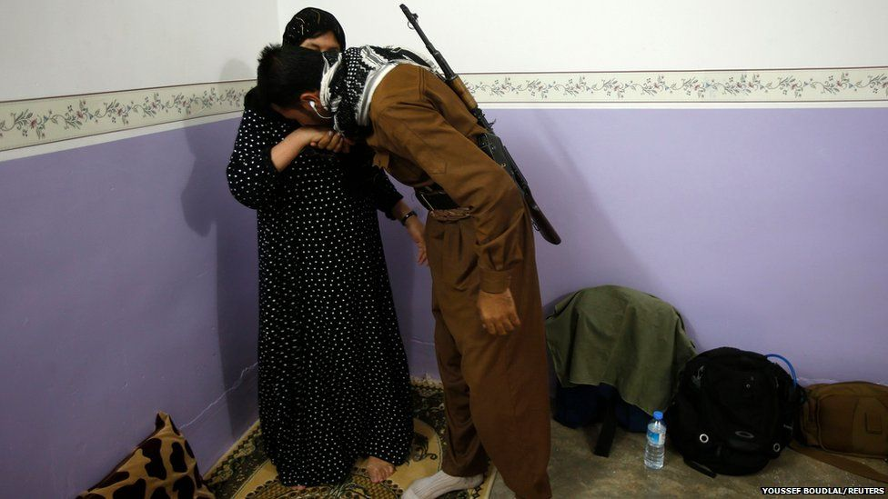 A mother says goodbye to her son in Tuz Khurmatu, Iraq