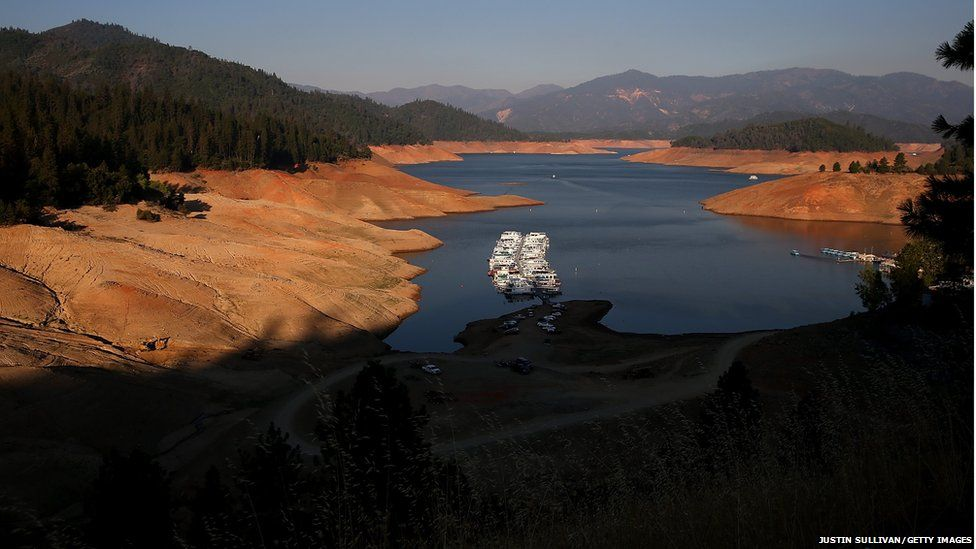Houseboats are dwarfed by the steep banks of Shasta Lake at Bridge Bay Resort in Redding, California