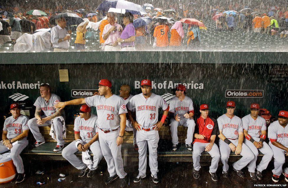 Members of the Cincinnati Reds watch from the dugout as heavy rain falls