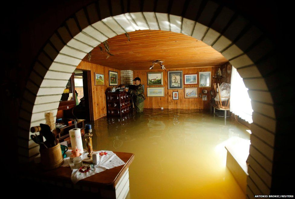 A man looks through his belongings at his flooded home in Zazina village, central Croatia